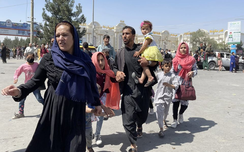An Afghan family rushes to the airport as they flee the Afghan capital of