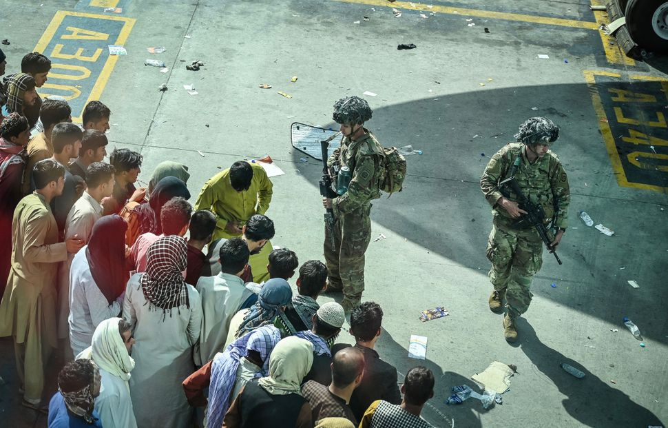 U.S. soldiers stand guard as Afghan people wait at the Kabul airport on Aug. 16, 2021.