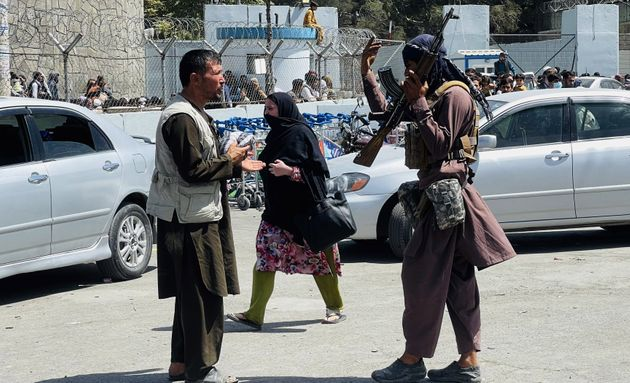 Taliban members are seen near Hamid Karzai International Airport as thousands of Afghans rush to