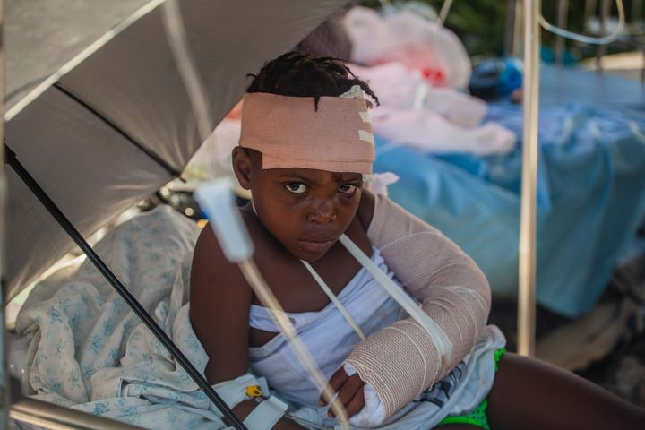 LES CAYES, HAITI - AUGUST 15:  A boy is tended to outside Les Cayes General Hospital after a 7.2-magnitude earthquake struck