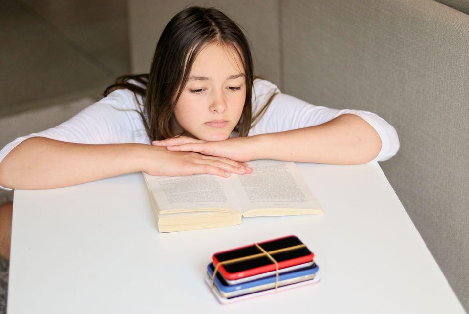 책을 펼쳐둔 채 꽁꽁 묶인 전자 기기를 바라보는 소녀. 휴대 전화를 멀리하기란 쉽지