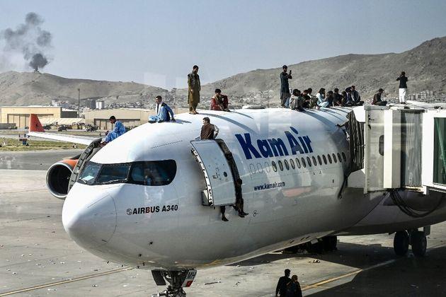 Des Afghans sur le toit d'un avion à l'aéroport de Kaboul le 16 août