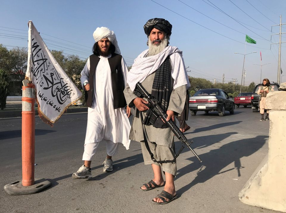 Taliban fighters stand outside the Interior Ministry in Kabul, Afghanistan, August 16,