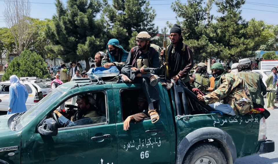 Taliban members are seen near Hamid Karzai International Airport as thousands of Afghans rush to...