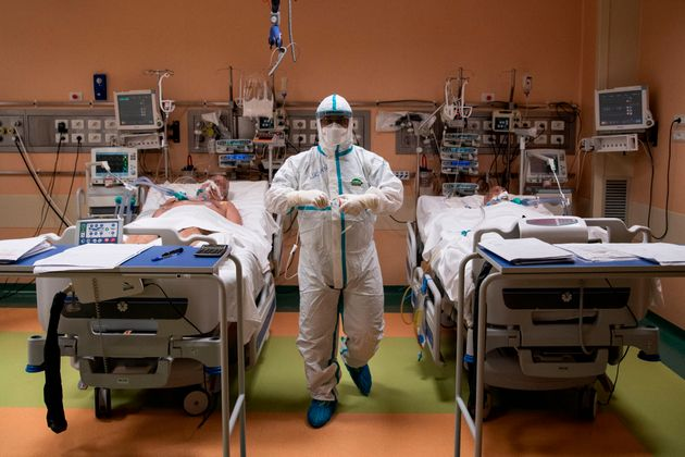 TOPSHOT - A doctor attends to patients in intensive care in the COVID-19 ward of the Maria Pia Hospital in Turin. (Photo by MARCO BERTORELLO / AFP) (Photo by MARCO BERTORELLO/AFP via Getty Images)