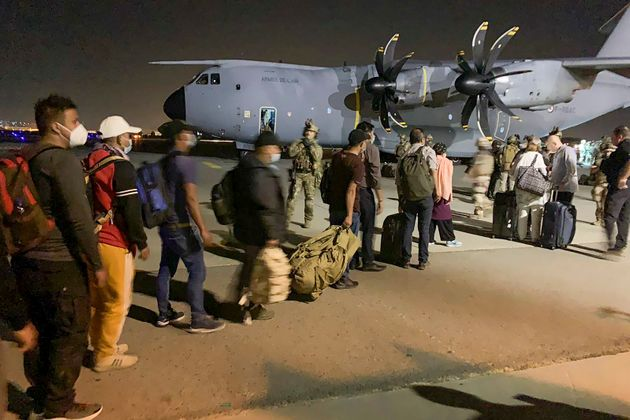 TOPSHOT - French and Afghan nationals line up to board a French military transport plane at the Kabul airport on August 17, 2021, for evacuation from Afghanistan after the Taliban's stunning military takeover of the country. (Photo by STR / AFP) (Photo by STR/AFP via Getty Images)