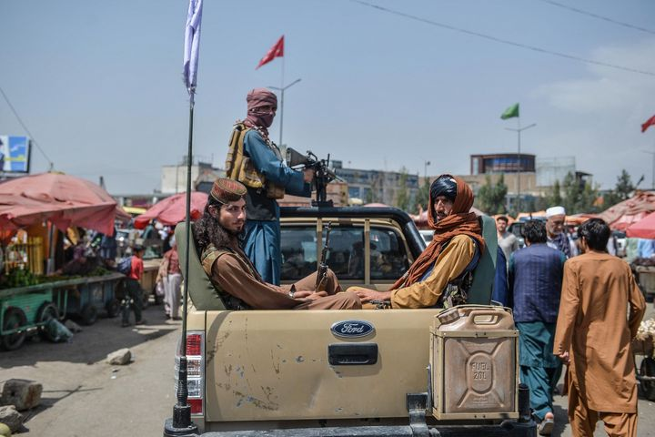 Taliban fighters on a pick-up truck move around a market area, flocked with local Afghan people at the Kote Sangi area of Kabul on Aug. 17, 2021.