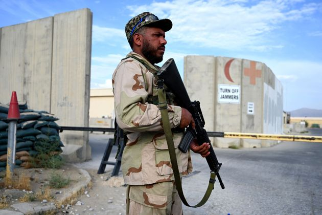 An Afghan National Army (ANA) soldier stands guard at a gate of a hospital inside the Bagram US air base...