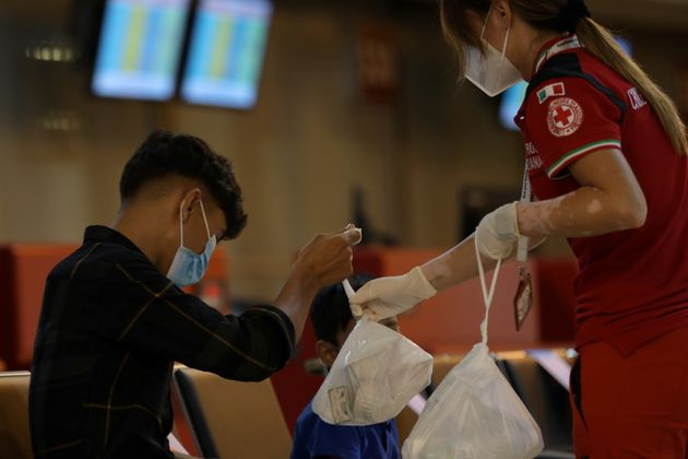 An Afghan boy receives a bag containing food from a Red Cross member after arriving at Fiumicino airport after Taliban insurgents entered Afghanistan's capital Kabul, in Rome, Italy, August 16, 2021. Picture taken August, 16, 2021. Italian Ministry of Defence/Handout via REUTERS ATTENTION EDITORS - THIS IMAGE HAS BEEN SUPPLIED BY A THIRD PARTY. NO RESALES. NO ARCHIVES