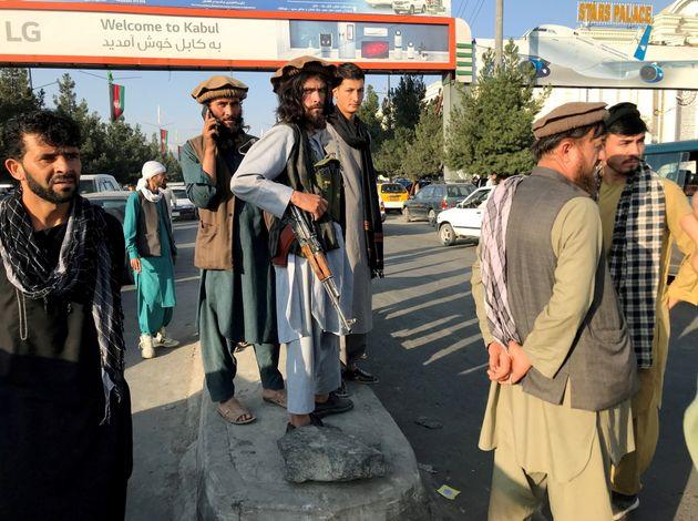 Des insurgés talibans patrouillent devant l'aéroport international Hamid Karzai de Kaboul,...