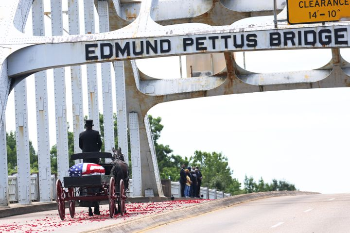 A horse-drawn carriage carrying the body of civil rights icon and former Rep. John Lewis (D-Ga.) crosses the Edmund Pettus Bridge as it prepares to pass members of his family on July 26, 2020, in Selma, Alabama.