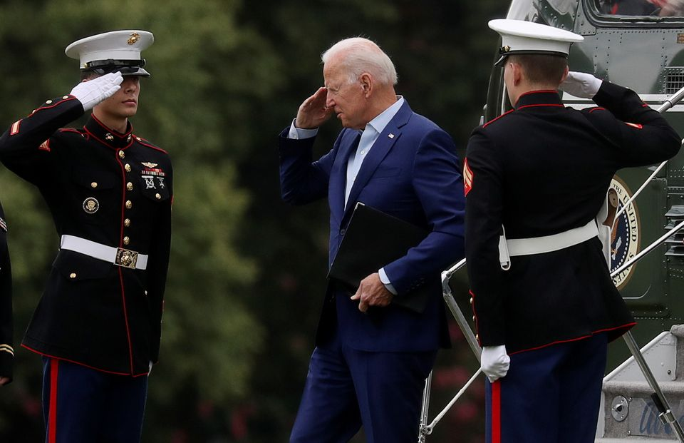 U.S. President Joe Biden returns a salute as he arrives at Fort McNair on his way back to the White House...