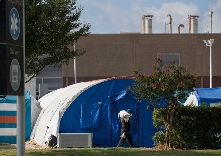 A construction crew sets up tents that hospital officials plan to use for an overflow of COVID-19 patients outside of Lyndon B. Johnson Hospital in Houston on Aug. 9.