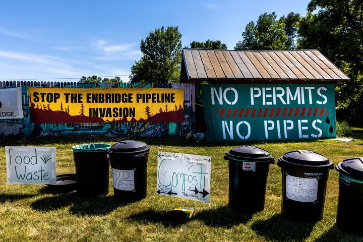 Pipeline protest signs form a backdrop to waste segregation bins at a campsite on the White Earth Nation Reservation near Wau