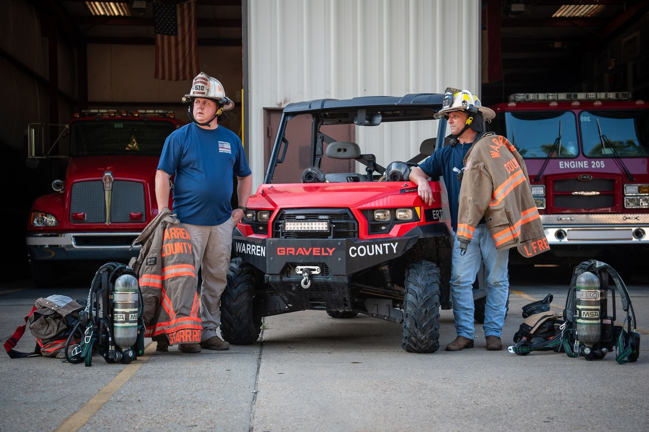 Warren County firefighters Shane Garrard (left) and Lamar Frederick in Vicksburg, Mississippi, in July. They're next to the utility task vehicle they used during the February 2020 gas leak in Satartia. <br><strong>Rory Doyle for HuffPost.</strong>