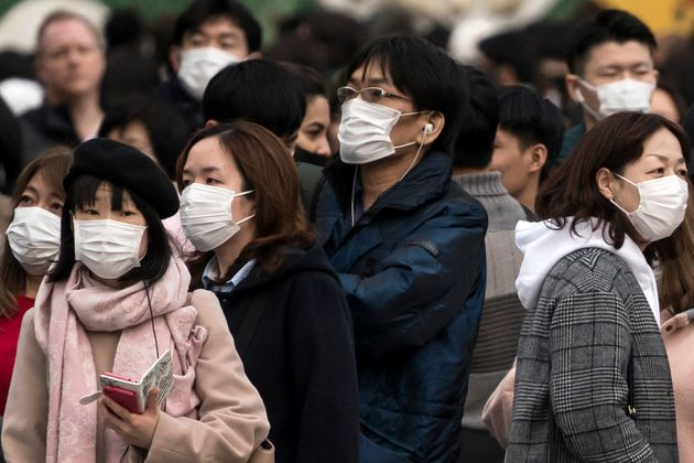 TOKYO, JAPAN: People wearing masks wait to cross a road in the Shibuya district in Tokyo, Japan. (Photo by Tomohiro Ohsumi/Getty Images)