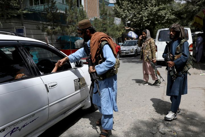 Taliban fighters stand guard at a checkpoint in Wazir Akbar Khan.