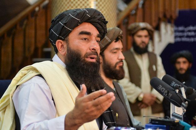 Taliban spokesperson Zabihullah Mujahid (L) gestures as he speaks during the first press conference in...