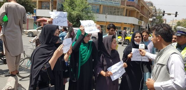 Afghan women, holding placards, gather to demand the protection of Afghan women's rights in front of...