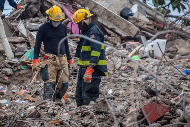 LES CAYES, HAITI - AUGUST 17: Firefighters remove debris in search of survivors after a 7.2-magnitude earthquake struck Haiti and as tropical storm Grace moves over Jamaica on August 17, 2021 in Les Cayes, Haiti. Rescue workers have been working among destroyed homes since the quake struck on Saturday and so far there are 1,941 dead and nearly 10,000 wounded. The epicenter was located about 100 miles west of the capital city Port-au-Prince. Tropical storm Grace hit the country on Monday and early Thursday causing floods and mudslides. (Photo by Richard Pierrin/Getty Images)