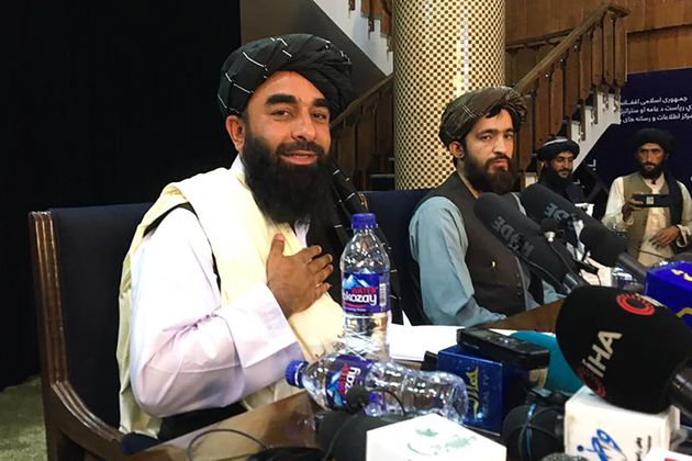 TOPSHOT - Taliban spokesperson Zabihullah Mujahid (L) attends the first press conference in Kabul on August 17, 2021, following their stunning takeover of Afghanistan. (Photo by Hoshang HASHIMI / AFP) (Photo by HOSHANG HASHIMI/AFP via Getty Images)