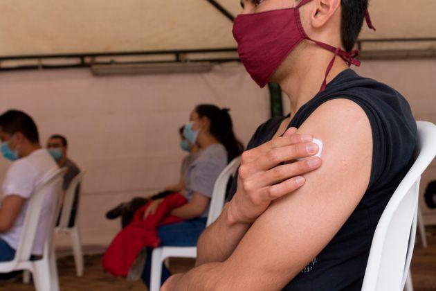 Paciente espera tras ser vacunada contra el