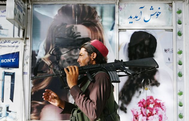A Taliban fighter walks past a beauty saloon with images of women defaced using a spray paint in Shar-e-Naw...