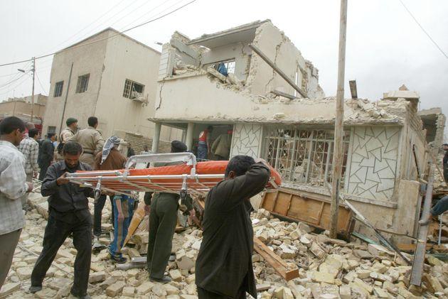 米軍の住宅密集地への空爆で破壊された民家から家財道具を運び出す市民(イラク・バグダッド、2003年3月)