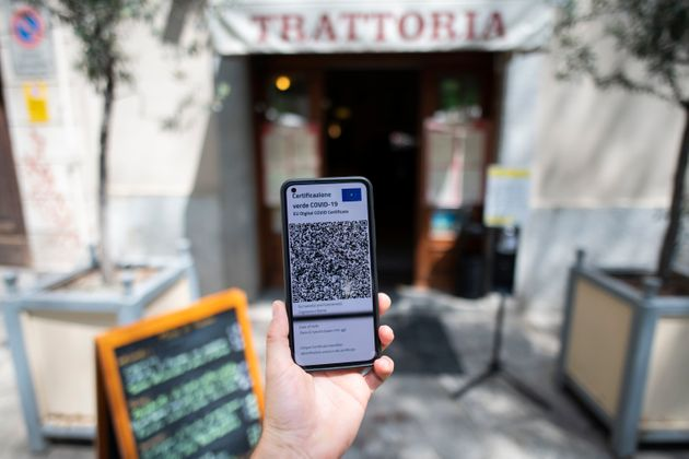 TURIN, ITALY - AUGUST 06: A hand show a one green pass in digital format outside on a restaurant on August 6, 2021 in Turin, Italy. The Italian government has approved a new rule concerning measures relating to the need to have a green pass if people want to sit at a table inside bars and restaurants and to access cinemas, theatre, museums and gyms. (Photo by Stefano Guidi/Getty Images)