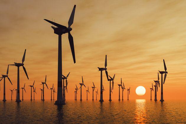 Offshore wind turbine farm at sunset.