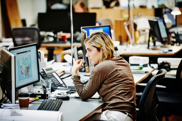 Female architect at workstation in office reviewing project with client on the phone