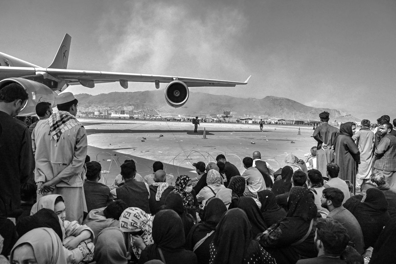 Afghans sit as they wait to leave the airport in Kabul on Monday after a stunningly swift end to Afghanistan's 20-year war.