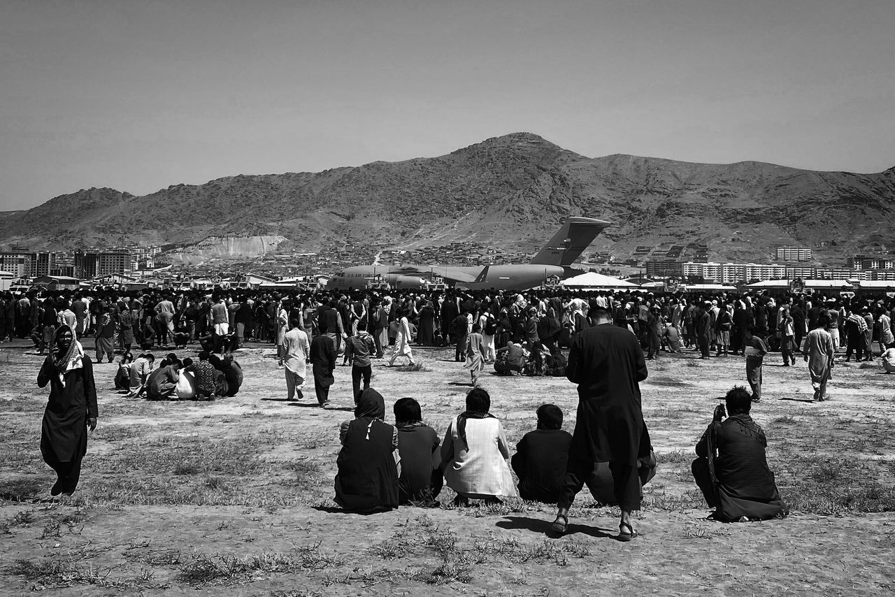 Hundreds of people gather near a U.S. Air Force C-17 transport plane at the perimeter of the international airport in Kabul on Monday.
