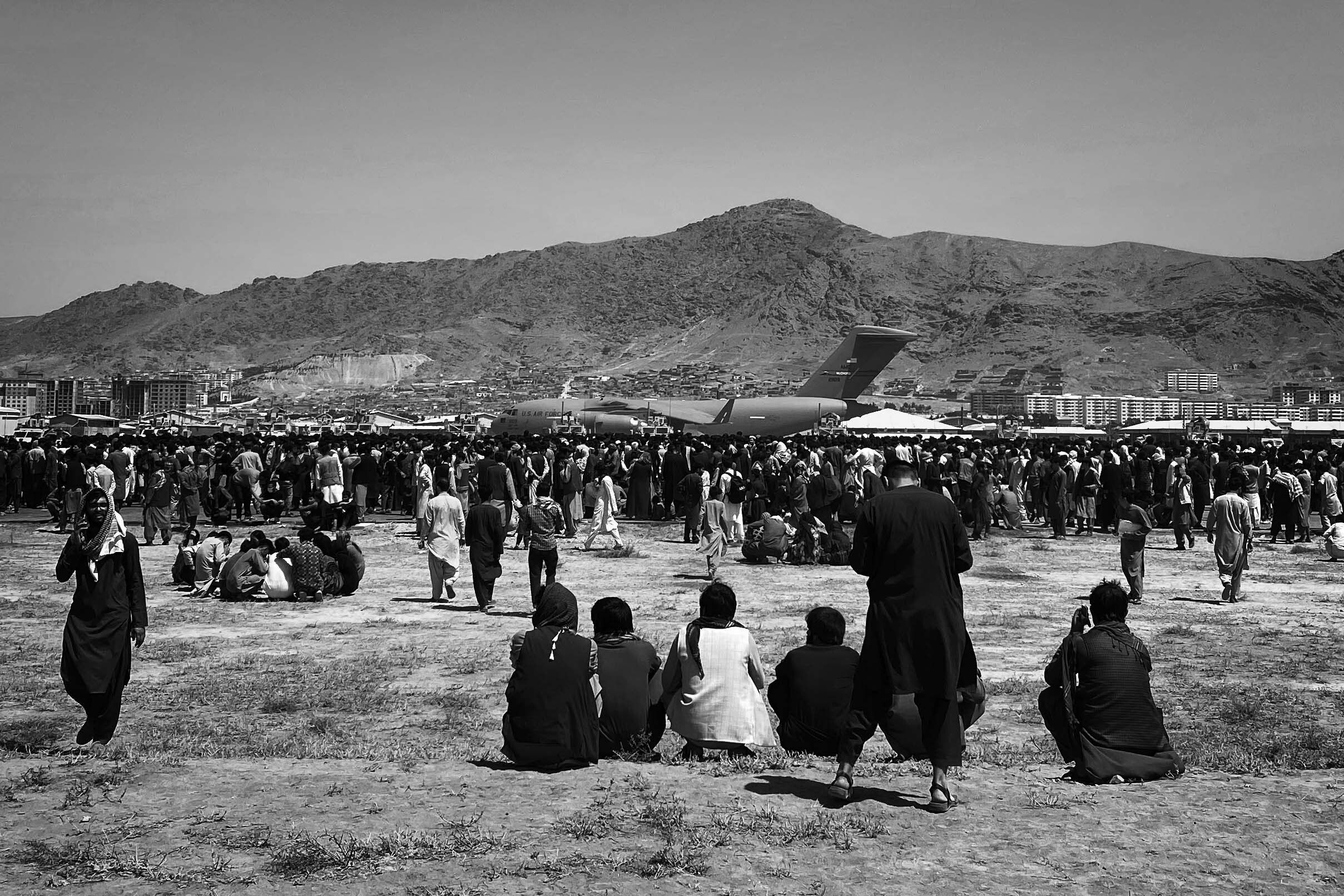Hundreds of people gather near a U.S. Air Force C-17 transport plane at the perimeter of the international airport in Kabul o