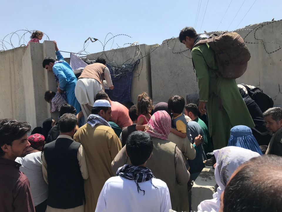 People struggle to cross the boundary wall of Kabul's Hamid Karzai International Airport on Monday to...