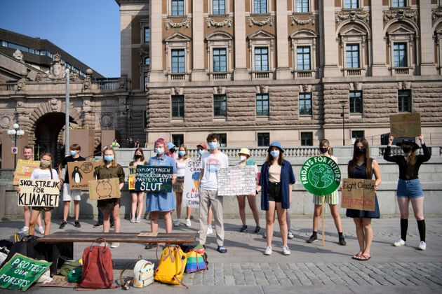 Swedish climate activist Greta Thunberg (2ndL) and other climate protesters gather for a protest against...