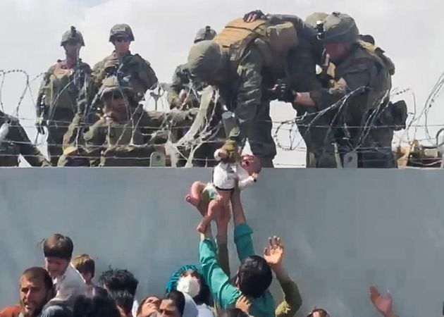 A baby is handed over to the American army over the perimeter wall of the airport for it to be evacuated,...