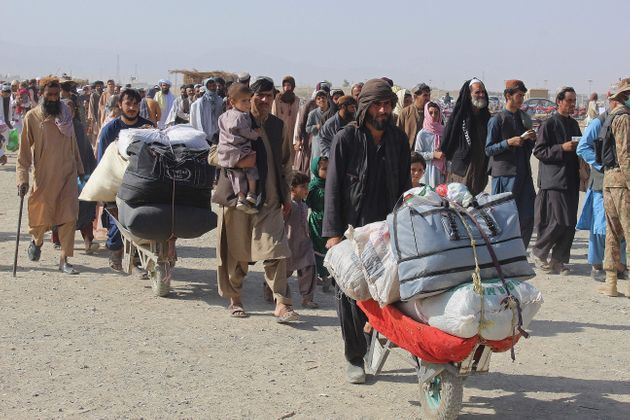 Afghan nationals arrive at the Pakistan-Afghanistan border crossing point in Chaman on August 20, 2021,...