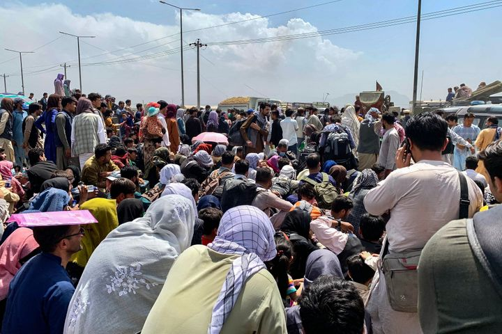 Afghans wait to board a U.S. military aircraft to leave the country.