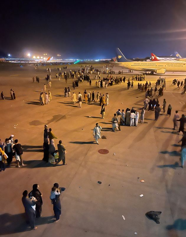 An undated amateur picture obtained by Reuters on August 19, 2021 shows people walking on the tarmac of the airport in Kabul, Afghanistan. Handout via REUTERS NO RESALES. NO ARCHIVES