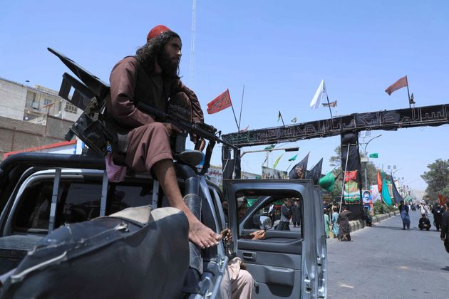 A Taliban fighter stands guard atop a vehicle near the site of an Ashura procession which is held to...