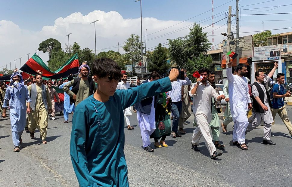 People carry the national flag at a protest held during the Afghan Independence Day in Kabul, Afghanistan...