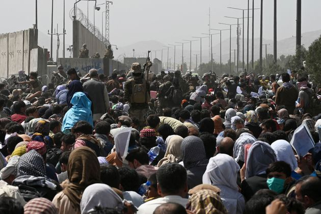 Afghans gather on a roadside near the military part of the airport in Kabul on August 20, 2021, hoping to flee from the country after the Taliban's military takeover of Afghanistan. (Photo by Wakil KOHSAR / AFP) (Photo by WAKIL KOHSAR/AFP via Getty Images)