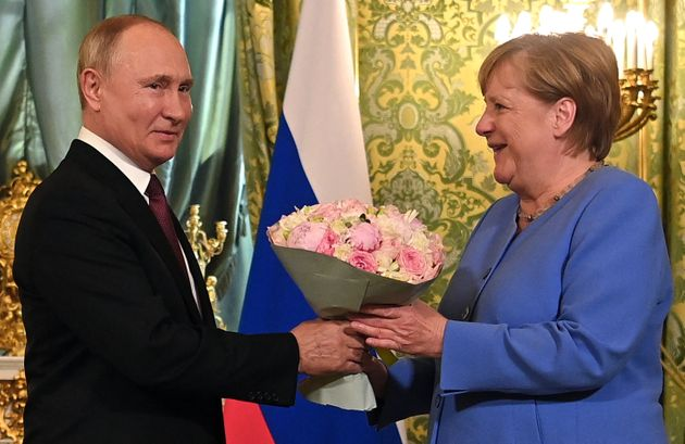 Russian President Vladimir Putin (L) welcomes German Chancellor Angela Merkel with a bouquet of flowers during their meeting at the Kremlin in Moscow on August 20, 2021. - The trip will be the 20th and last visit to Russia for Angela Merkel as German Chancellor, who bows out of politics following an election in Germany on September 26, 2021. (Photo by Evgeny ODINOKOV / SPUTNIK / AFP) (Photo by EVGENY ODINOKOV/SPUTNIK/AFP via Getty Images)
