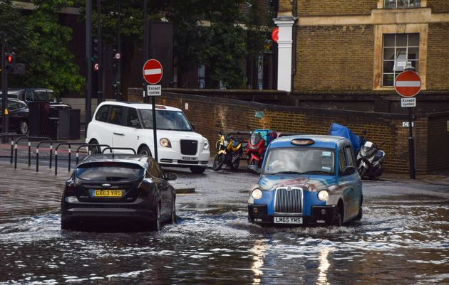 A taxi drives through a flooded Farringdon Lane in central London after a day of heavy rain in the capital...