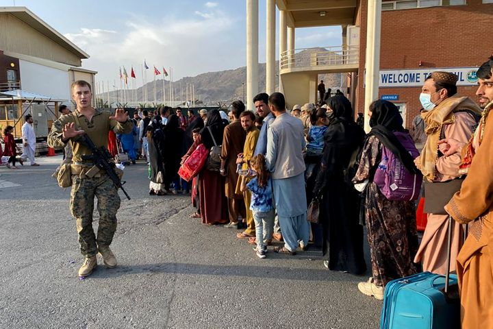 Afghan people line up to board a U.S. military aircraft to leave Afghanistan at the military airport in Kabul on Aug. 19 after Taliban's military takeover of Afghanistan.