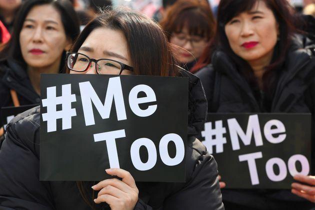 韓国ソウルで開かれた国際女性デーの抗議デモで、#MeTooムーブメントのカードを掲げる人々(2018年3月8日)