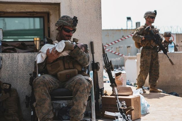 A U.S. Marine assigned to the 24th Marine Expeditionary Unit (MEU) holds a baby during an evacuation at Hamid Karzai International Airport, Kabul, Afghanistan, in this photo taken on August 20, 2021. Sgt. Isaiah Campbell/U.S. Marine Corps/Handoutvia REUTERS THIS IMAGE HAS BEEN SUPPLIED BY A THIRD PARTY.