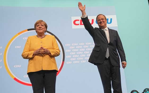 21 August 2021, Berlin: Armin Laschet, candidate for chancellor of the CDU/CSU, federal chairman of the CDU and state premier of North Rhine-Westphalia, stands next to Chancellor Angela Merkel (CDU) on stage at the central campaign kick-off of the CDU and CSU. With the event at the Tempodrom, the Union wants to start the hot phase of the campaign for the 2021 federal election. Photo: Michael Kappeler/dpa (Photo by Michael Kappeler/picture alliance via Getty Images)