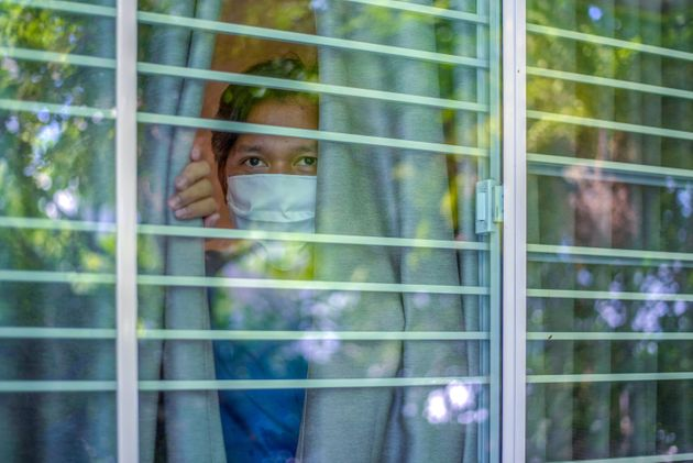 Man wearing a protective mask is looking out of the window. Home quarantine for 14 days due to the coronavirus COVID-19 epidemic.
